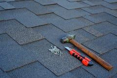 Schließen Sie herauf Ansicht über Asphaltschindeln auf einem Dach mit Hammer, Nägeln und Teppichmesserhintergrund lizenzfreies stockfoto