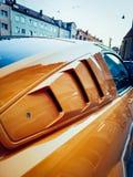 Schließen Sie herauf Ansicht über einen orange und schwarzen Mustang stockfotos
