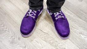 Schließen Sie herauf Ansicht über Mann ` s Beine in den dunklen Jeans und in den Lederstiefeln Stockfoto