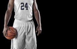 Schließen Sie herauf Ansicht des Basketball-Spielers auf einem schwarzen Hintergrund Lizenzfreie Stockfotografie