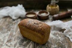 Schließen Sie herauf Ansicht des frischen braunen knusperigen Brotlaibs, der auf dem Holztisch liegt, der mit Mehl besprüht wird Stockfotos