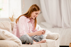 Schließen Sie herauf Ansicht des jungen hübschen Mädchens, das auf Sofa stillsteht lizenzfreie stockbilder
