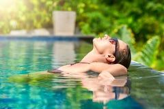 Schließen Sie herauf Ansicht einer attraktiven jungen Frau, die auf einem Badekurort ` s s sich entspannt Stockbild