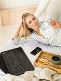 Schließen Sie herauf Ansicht eines dreamig, das freiberuflich tätige Frau zu Hause bearbeiten Schlafzimmer, Laptop und Telefon Fr Stockbild