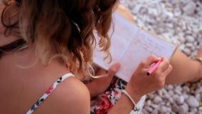 Schließen Sie herauf Ansicht eines Frauenschreibens in ihrem Tagebuch bei dem Sonnenuntergang, der auf einem Strand sitzt stock video