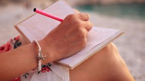 Schließen Sie herauf Ansicht eines Frauenschreibens in ihrem Tagebuch bei dem Sonnenuntergang, der auf einem Strand sitzt stock footage