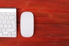 Schließen Sie herauf Ansicht eines Geschäftsarbeitsplatzes mit drahtlosen ComputerTasten und der Maus auf altem rotem natürlichem Lizenzfreie Stockbilder