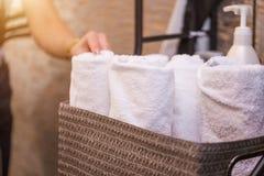 Schließen Sie herauf Ansicht von Badekurortthemagegenständen auf grauem Hintergrund Weiße Frotteestoffe im Korb stockfotos