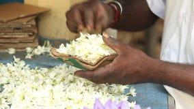 Schließen Sie herauf Ansicht von den Händen, die Blumenvorkehrungen für Tempelangebote in Kandy, Sri Lanka treffen stock video