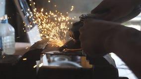 Schließen Sie herauf Arme des sägenden Metalls des männlichen Schweißers mit einer Kreissäge in der Garage Männliche Hände des Be stock footage