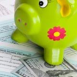 Schließen Sie herauf Atelieraufnahme von hundert Dollar Banknote und Sparschwein über US-Steuerformular Stockfotografie