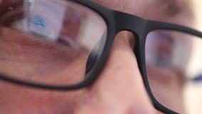 Schließen Sie herauf Augen eines Mannes mit Gläsern, der sorgfältig den Monitor oder die Arbeitsgeräte betrachtet stock video footage