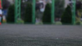Schließen Sie herauf aut Fokus von Männer ` s Füßen, die durch Fußballplatz im Stadtpark spielen und laufen Flache Tiefe des Feld stock video