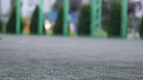 Schließen Sie herauf aut Fokus von Männer ` s Füßen, die durch Fußballplatz im Stadtpark spielen und laufen Flache Tiefe des Feld stock footage