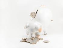 Schließen Sie herauf beautyful Sparschwein und Münzen auf weißem Hintergrund für Finanz- und Einsparungsgrafik mit copyspace Stockfotos