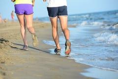 Schließen Sie herauf Beine des jungen Paarmannes und -frau, die in den Sand auf dem Ufer des Strandes durch das Meer während sonn Lizenzfreies Stockfoto