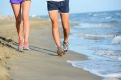 Schließen Sie herauf Beine des jungen Paarmannes und -frau, die in den Sand auf dem Ufer des Strandes durch das Meer während sonn Stockbilder