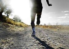 Schließen Sie herauf Beine und Füße extremen Cross Country-Mannbetrieb und -training auf der ländlichen Bahn, die bei Sonnenunter Lizenzfreie Stockfotografie