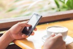 Schließen Sie herauf beweglichen Handgebrauch Smartphone und trinken Sie Kaffee Lizenzfreie Stockfotos