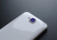 Schließen Sie herauf Bild der Kamera des weißen intelligenten Telefons auf schwarzer Tabelle Stockbilder