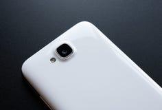 Schließen Sie herauf Bild der Kamera des weißen intelligenten Telefons auf schwarzer Tabelle Lizenzfreies Stockfoto