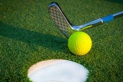 Schließen Sie herauf Bild des Golflochs mit Ball und putten Sie Stockbilder