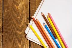 Schließen Sie herauf Bild des leeren Papiers und der bunten Bleistifte auf altem Holztisch Lizenzfreie Stockfotografie