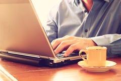 Schließen Sie herauf Bild des Mannes, der Laptop nahe bei Tasse Kaffee verwendet Retro- Art-Bild Selektiver Fokus Stockfotos