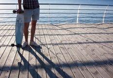 schließen Sie herauf Bild des Mannes mit Skateboard auf dem Strand Stockfotografie