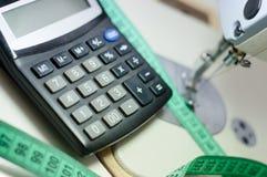 Schließen Sie herauf Bild des Taschenrechners an der weißen Nähmaschine und am grünen messenden Band lizenzfreie stockfotos