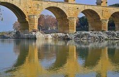 Schließen Sie herauf Bild des unteren Bogenniveaus von Pont DU Gard mit klarer Reflexion auf Gardon-Fluss Stockbild