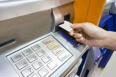 Schließen Sie herauf Bild einer menschlichen Hand, die eine Kreditkarte in AN einfügt Stockfotografie