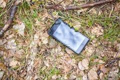 Schließen Sie herauf Bild eines defekten Handys auf einem Boden im Park Lizenzfreie Stockfotografie