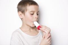 Schließen Sie herauf Bild eines netten kleinen Jungen, der Inhalator für Asthma verwendet lizenzfreie stockbilder