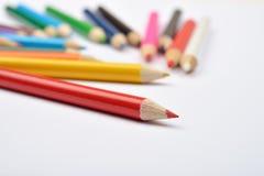 Schließen Sie herauf Bild vieler kleinen farbigen Bleistiftzeichenstifte auf Weiß Stockfotografie
