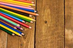 schließen Sie herauf Bild von bunten Bleistiften auf altem Holztisch Stockbilder