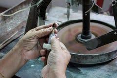 Schließen Sie herauf Bild von Händen eines traditionellen Ausschnitts der Person einen Edelstein Stockfotografie