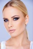 Schließen Sie herauf blonde Frau mit blauen Augen Stockfotos