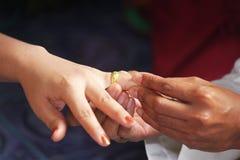 Schließen Sie herauf Bräutigam Put den Ehering auf Braut Stockfoto