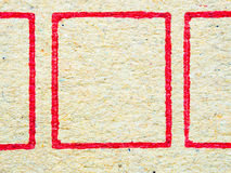 Schließen Sie herauf braune Wellpappe mit rotem Quadrat Stockbilder