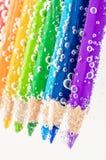 Schließen Sie herauf bunte hölzerne Bleistifte im Sodawasser Stockfoto