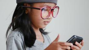 Schließen Sie herauf das asiatische kleine Mädchen des Schusses, das mobilen Smartphone verwendet stock footage