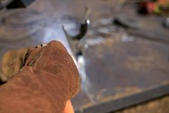 Schließen Sie herauf das Bild der Schweißerhand einen roten Schweißhandschuh-Sicherheitsschutz tragend lizenzfreie stockfotos