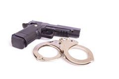 Schließen Sie herauf das Gewehr und Handschellen, die auf Weiß lokalisiert werden Stockfotografie