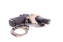 Schließen Sie herauf das Gewehr und Handschellen, die auf Weiß lokalisiert werden Lizenzfreie Stockfotos