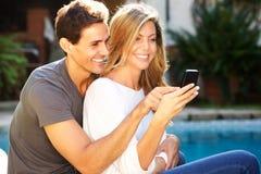 Schließen Sie herauf das glückliche Paar, das draußen durch das Pool sitzt, das selfie nimmt Stockfotos