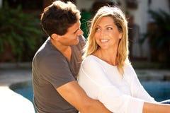 Schließen Sie herauf das glückliche Paar, das zusammen draußen durch Pool sitzt Lizenzfreie Stockfotos