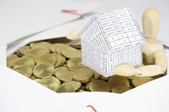 Schließen Sie herauf das hölzerne blinde haltene Haus, das durch Goldmünzen umgeben wird Stockbild