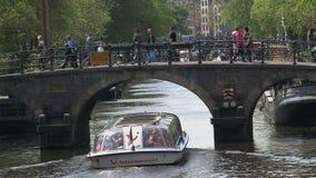 Schließen Sie herauf das Kanalboot, das durch eine Brücke in Amsterdam überschreitet stock video footage
