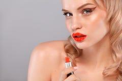 Schließen Sie herauf das Porträt des attraktiven Mädchens ihre Lippen rouging Sie hält roten Lippenstift in der Maus Lokalisiert  stockbild